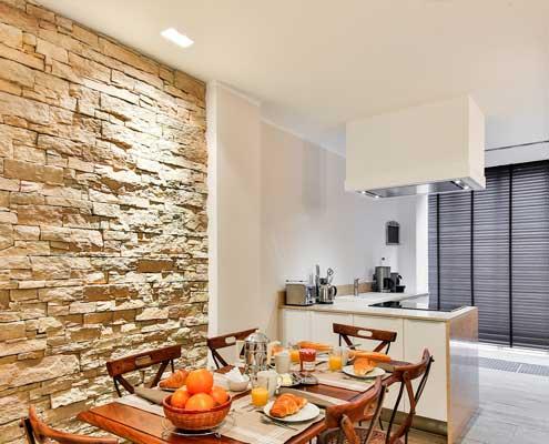 cocina reformada con pared de pierda